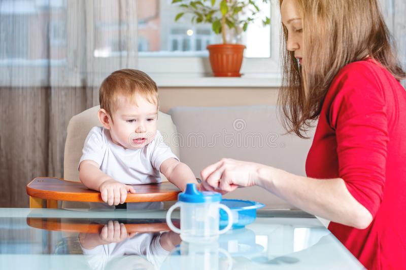 Mother feeding the baby holding hand with a spoon of food. Healthy baby nutrition. The emotions of a child while eating. Mom feeding the baby holding out her stock image