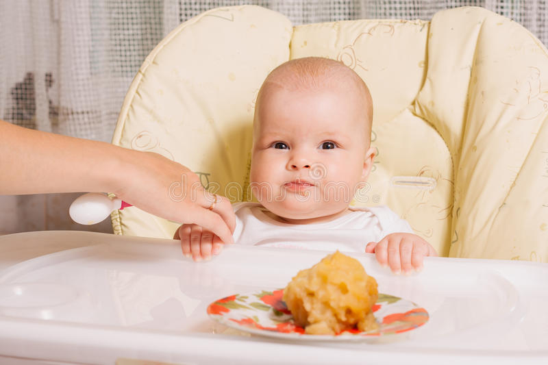 Mother feeding baby with a spoon. baked apple royalty free stock photo