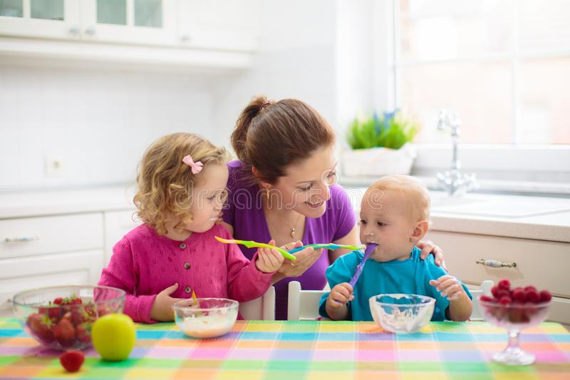 Mother feeding child. Mom feeds kid fruit. Mother feeding child fruit and yoghurt. Mom feeds kid in white kitchen. Baby boy and girl sitting in high chair eating stock photography