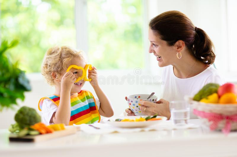 Mother feeding child. Mom feeds kid vegetables stock photos