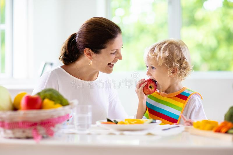 Mother feeding child. Mom feeds kid vegetables royalty free stock images