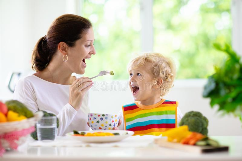 Mother feeding child. Mom feeds kid vegetables royalty free stock photography
