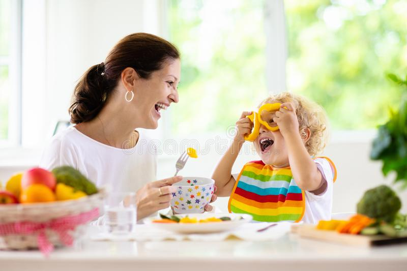Mother feeding child. Mom feeds kid vegetables royalty free stock photo