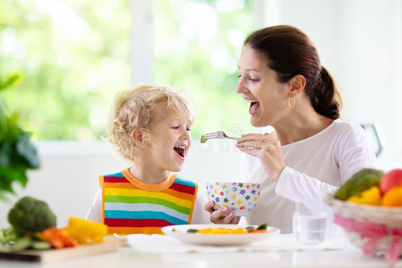 Mother feeding child. Mom feeds kid vegetables stock images