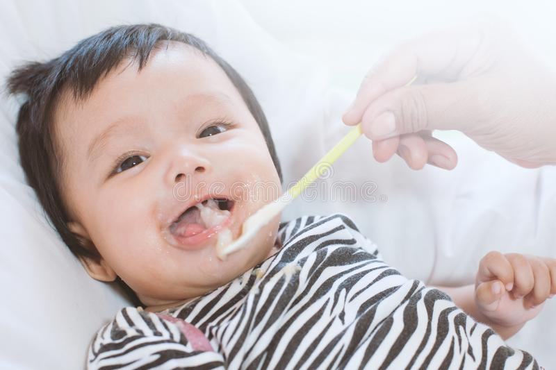 Mother feeding cute asian baby girl with a spoon at home royalty free stock images
