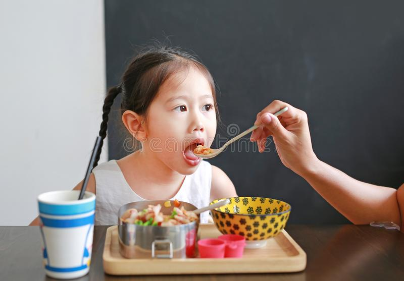 Mother feeding food for her daughter stock photos