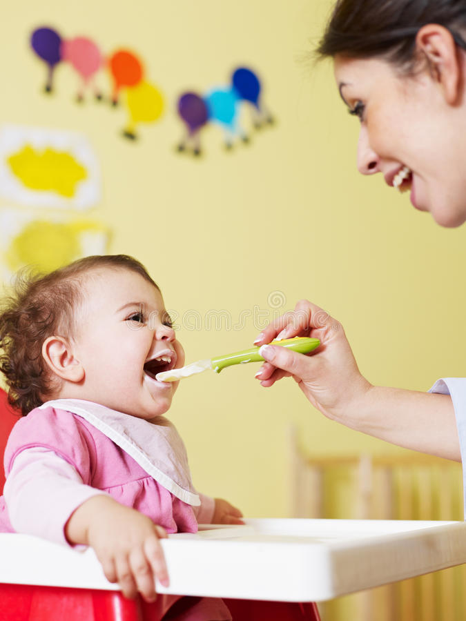 Mother feeding her baby stock images