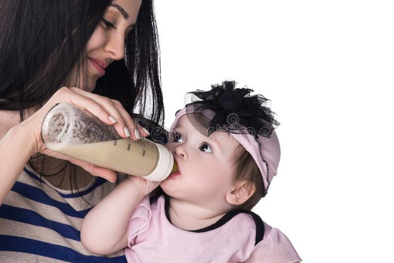 Mother feeding her baby girl from a bottle stock photo