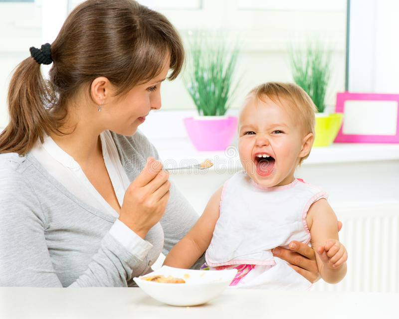 Mother Feeding Her Baby. Girl with a Spoon royalty free stock photos