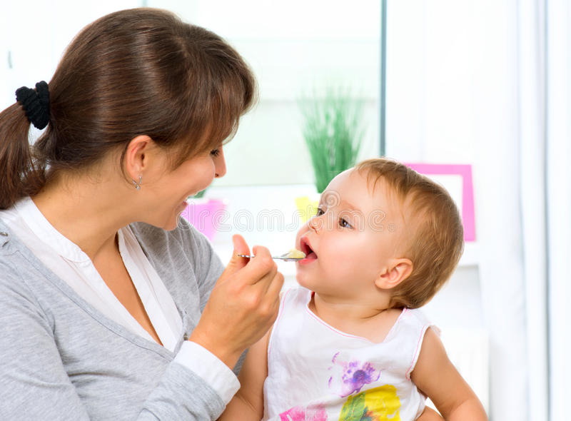 Mother Feeding Her Baby. Girl with a Spoon stock photos