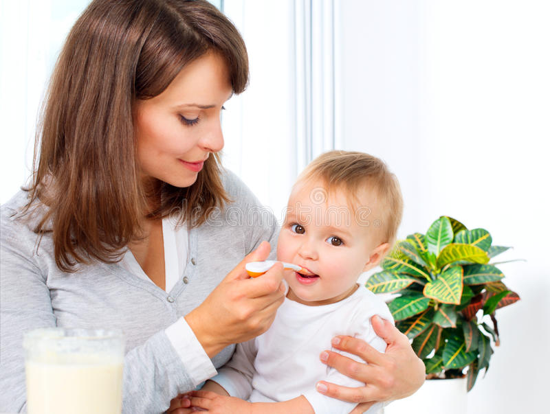 Mother Feeding Her Baby. Girl with a Spoon royalty free stock images