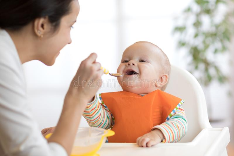 Mother feeding her baby with spoon. Mother giving healthy food to her adorable child at home royalty free stock photography