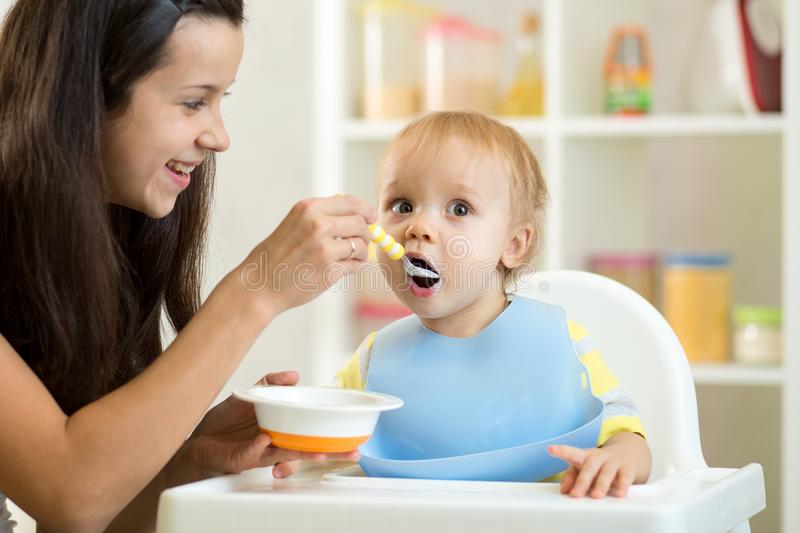 Mother feeding her baby with spoon. Mother giving healthy food to her adorable child at home royalty free stock photo