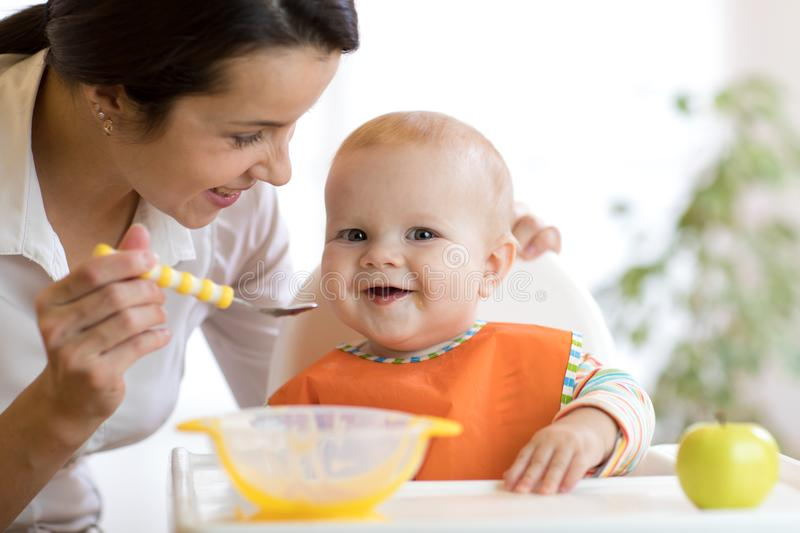 Mother feeding her baby with spoon. Mother giving healthy food to her adorable child at home stock photo