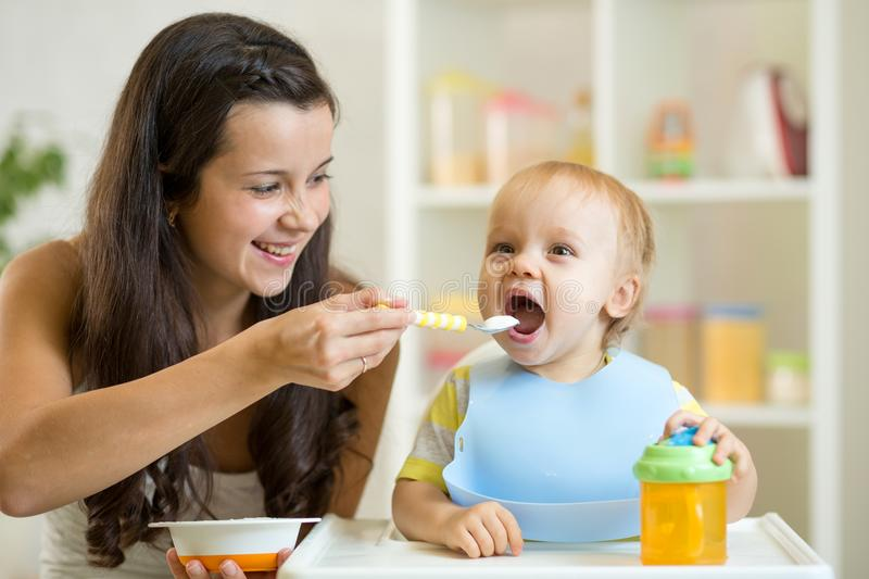 Mother feeding her baby with spoon. Mother giving healthy food to her adorable child at home royalty free stock image