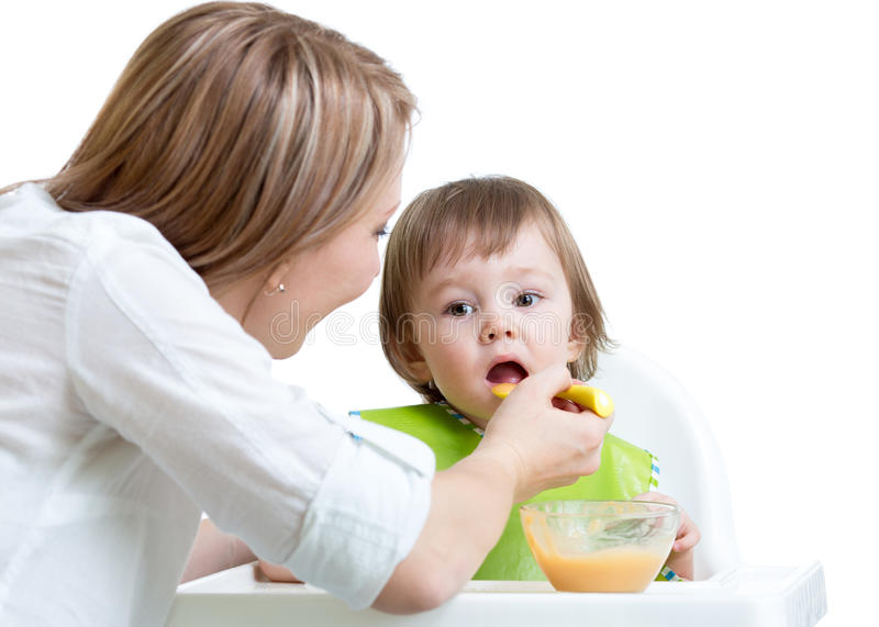 Mother feeding kid stock photography