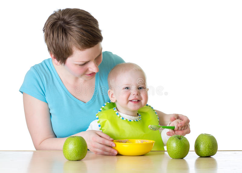 Mother feeding kid boy with spoon isolated on white stock photo