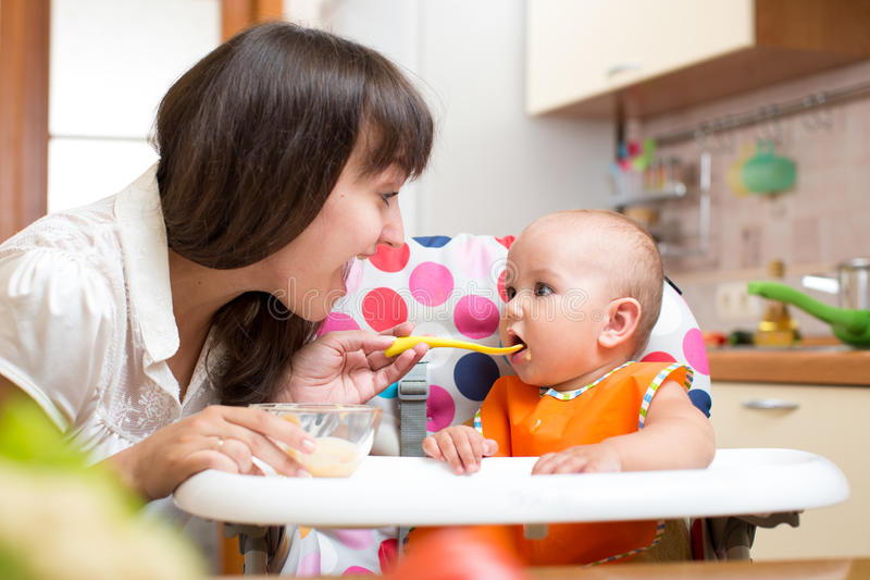 Mother feeding kid with spoon indoors royalty free stock image