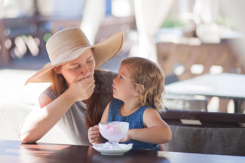 Mother and daughter eating ice cream at the restaurant. royalty free stock photo