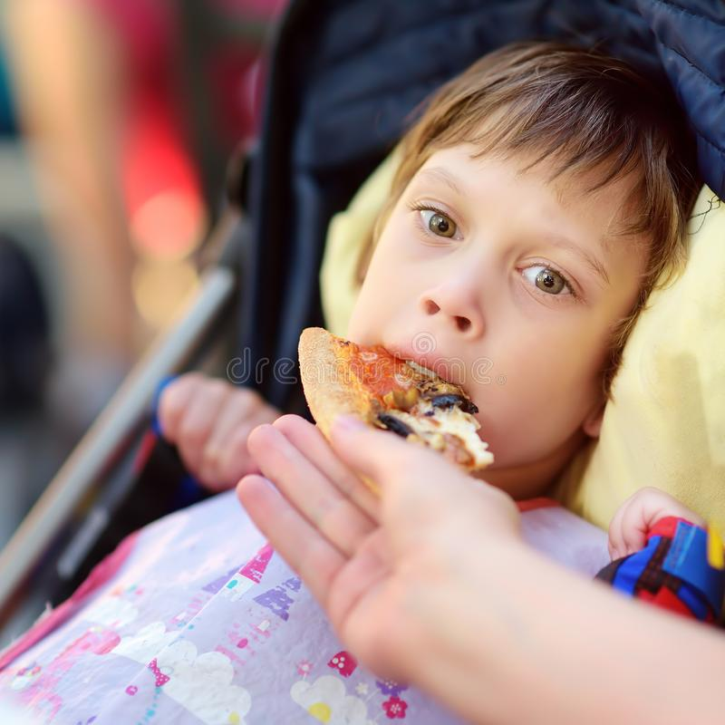 Mother feeding pizza`s a little disabled girl in a wheelchair. Child cerebral palsy. Inclusion. Family with disabled kid royalty free stock image