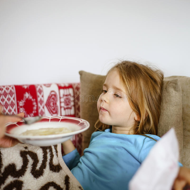 Mother feeding taken ill daughter by semolina stock photography