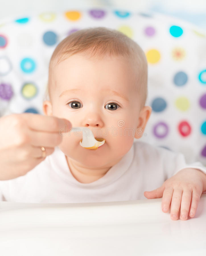 Mother feeds funny baby from spoon stock photos