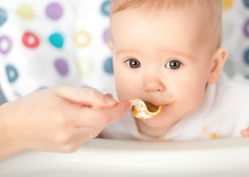 Mother feeds funny baby from spoon royalty free stock photography
