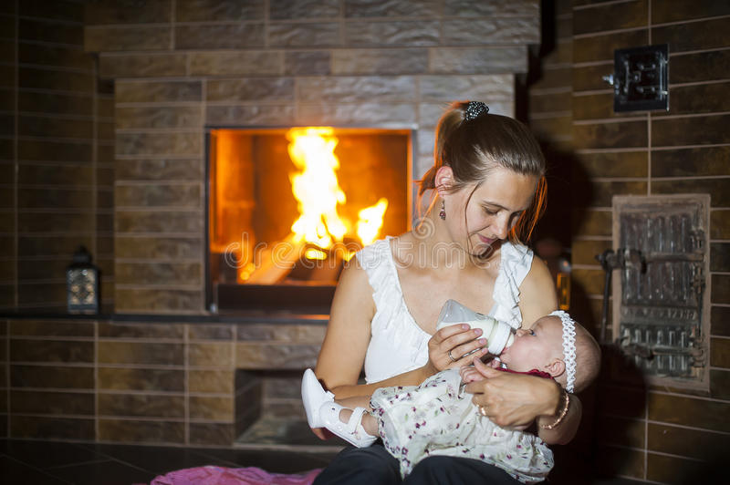 Mother feeds her baby at the fireplace stock photo