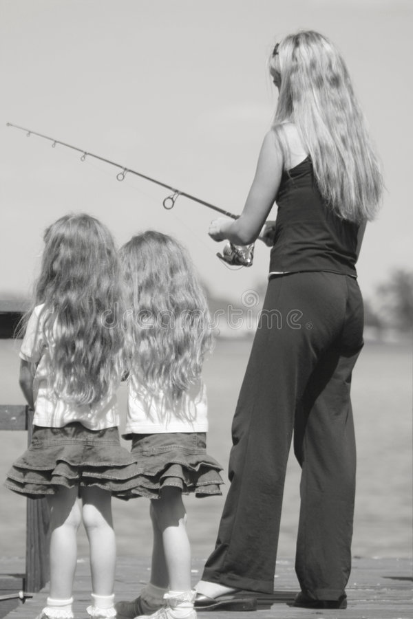 Mother fishing with kids - black & white royalty free stock image