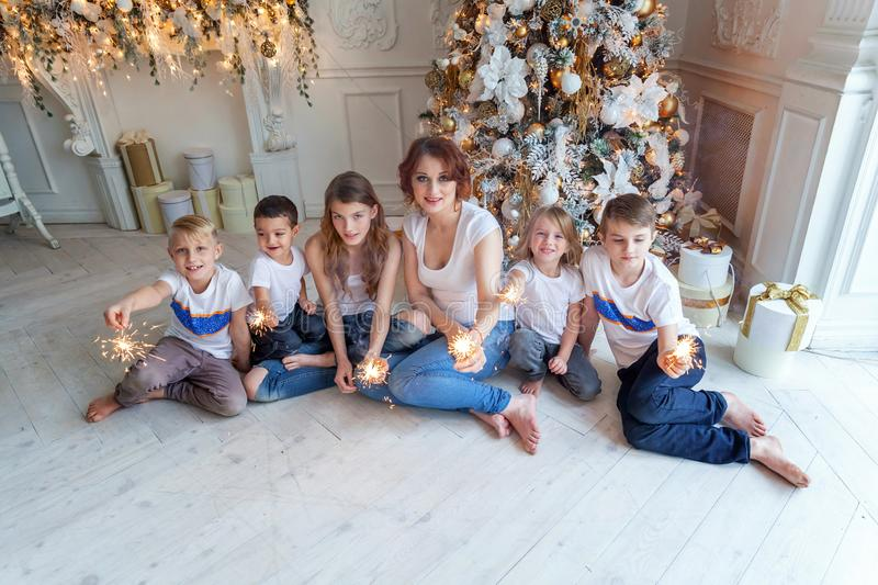 Mother and five children playing sparkler near Christmas tree at home royalty free stock photo
