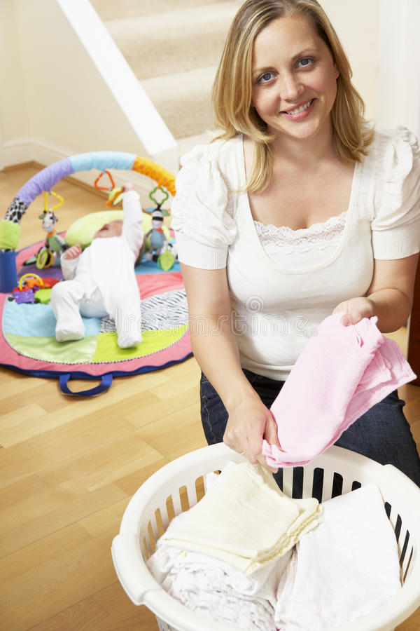 Mother Folding Baby Clothes At Home Stock graphy