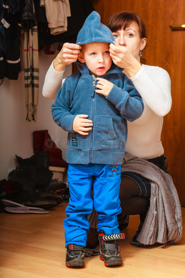 Mother in front hallway putting on child coat royalty free stock images
