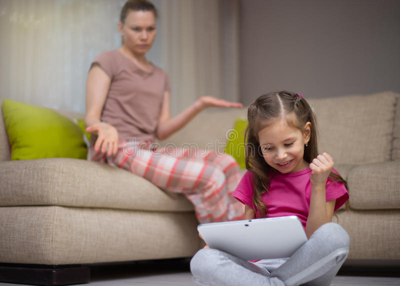Mother frustrating that her daughter playing video games. royalty free stock photos