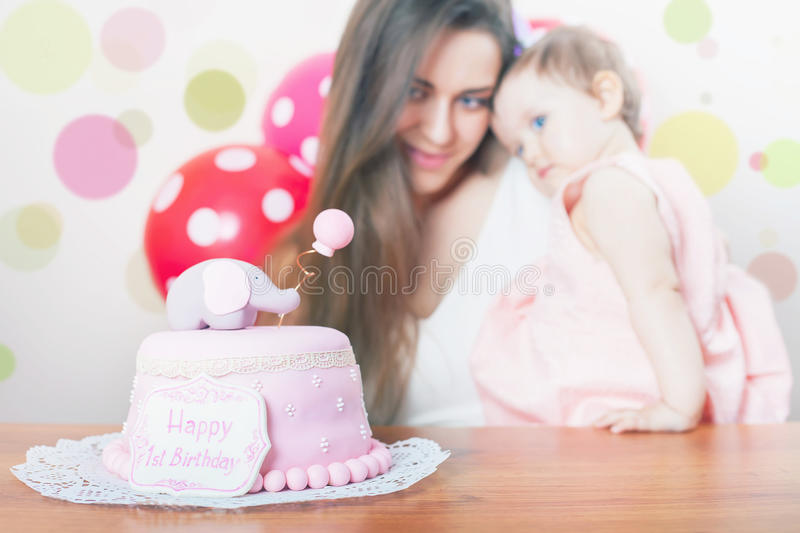 Mother with funny baby celebrating first birthday. Cake. Mother with funny baby celebrating first bithday. Cake is surprise for child. Make a first wish. Desire stock photo