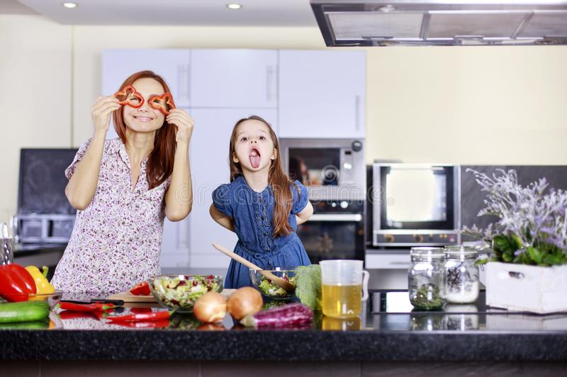 Mother and funny daughter playing in the kitchen with vegetables royalty free stock photography