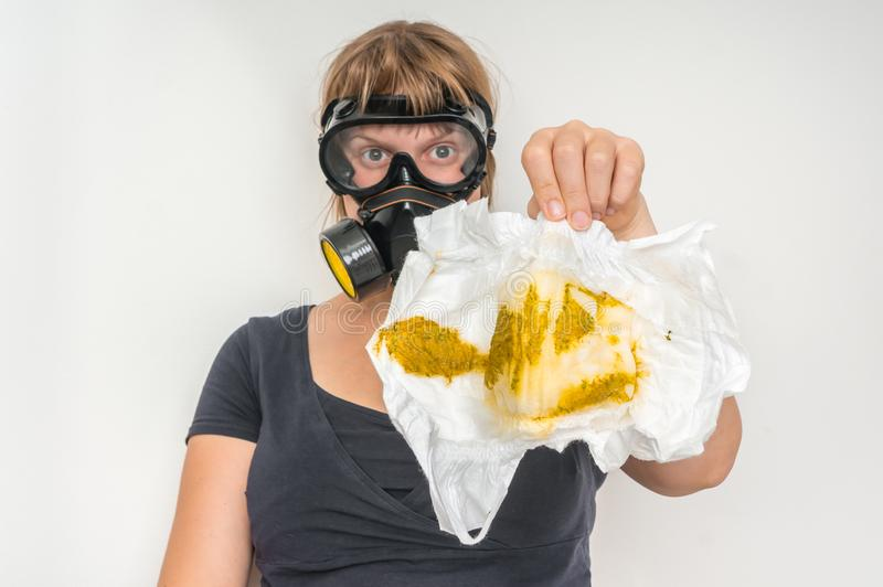 Mother with gas mask changing smelly diaper. Baby care concept stock image