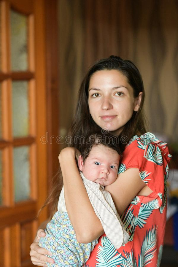Mother gently hugs the baby. at home. Mom and newborn baby. Mom hugs and holds the newborn baby in her arms, the newborn sleeps in royalty free stock photos