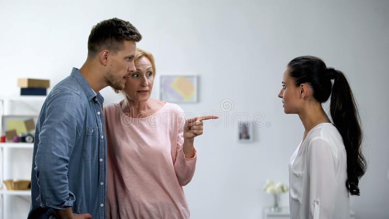 Mother getting on son side in conflict with wife, interference in relationship. Stock photo stock images