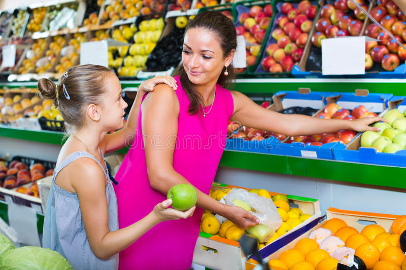 Mother with girl picking apples in shop stock image