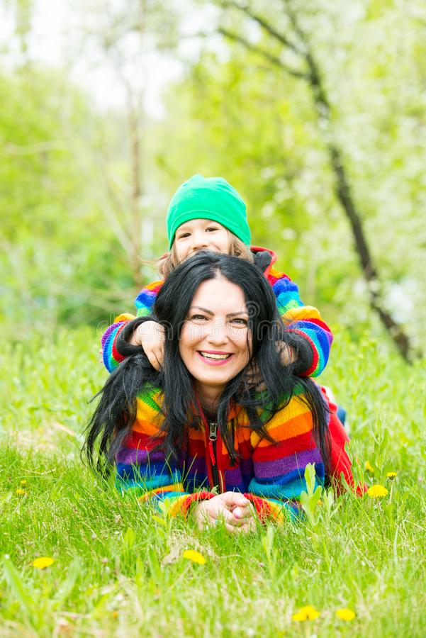 Mother give piggyback to her son. Mother giving piggyback to her son and laying on grass in park stock photo
