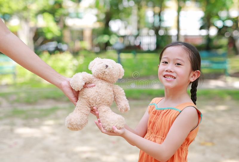 Mother give a teddy bear doll for her daughter in the park outdoor. Gift from mom for girls. Close-up happy kid with smiling royalty free stock image