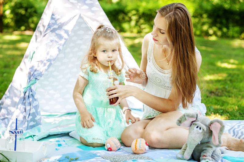 Mother gives baby drink juice. Picnic. The concept of family lifestyle and love. stock photos