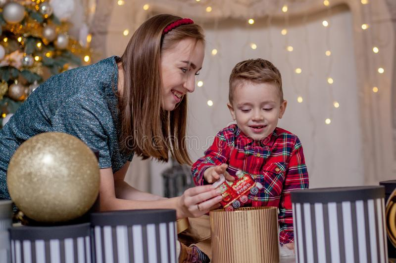 Mother gives Christmas gift to his little son for a New Year. Mom and son opening Christmas presents royalty free stock images