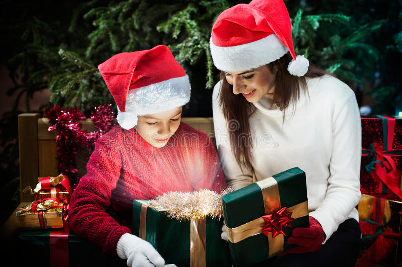 Mother gives her child a Christmas gift box with light rays. In a magical day royalty free stock image
