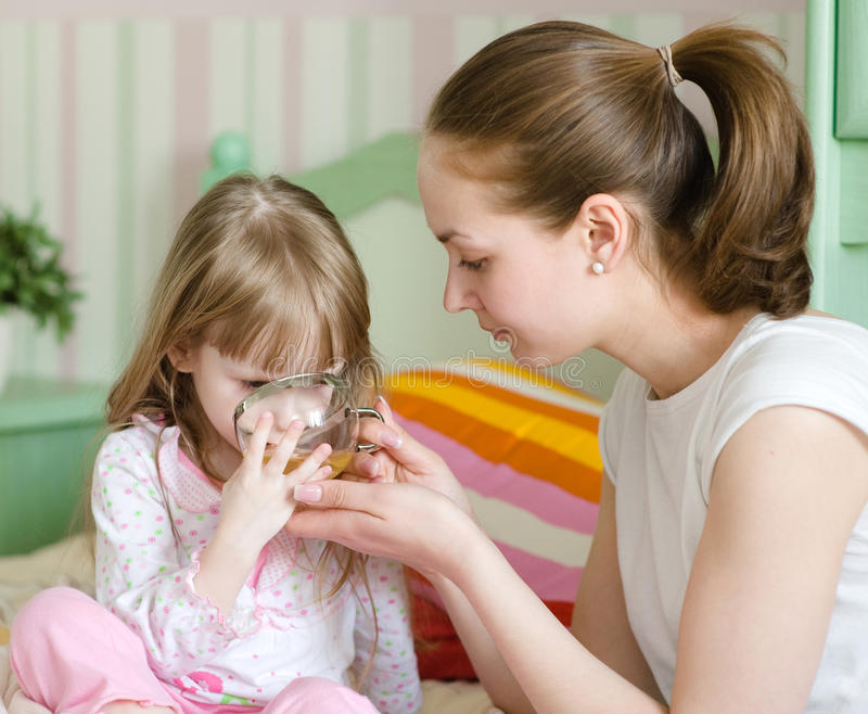 Mother gives to drink to the sick child.  royalty free stock photography