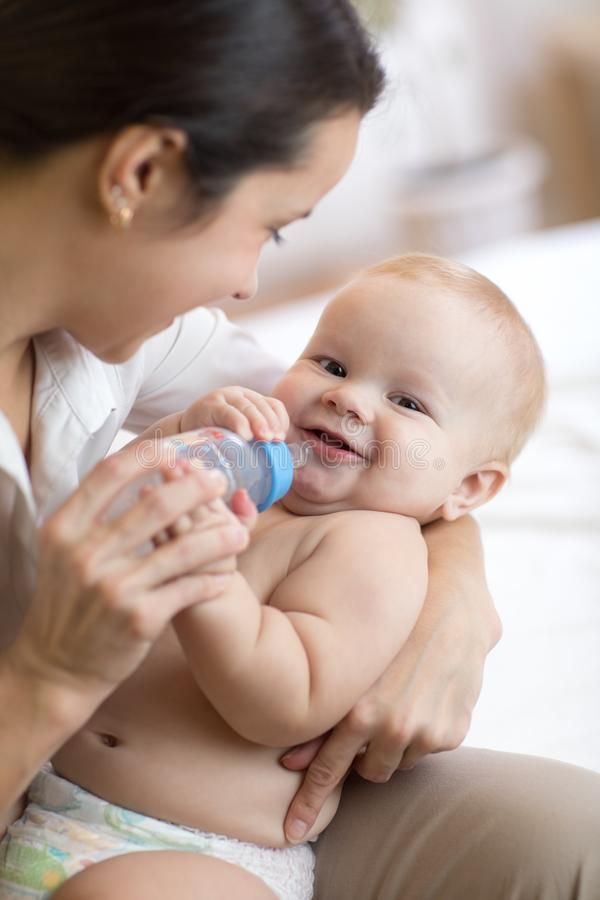 Mother Giving Baby Water From The Bottle Sitting On The ...