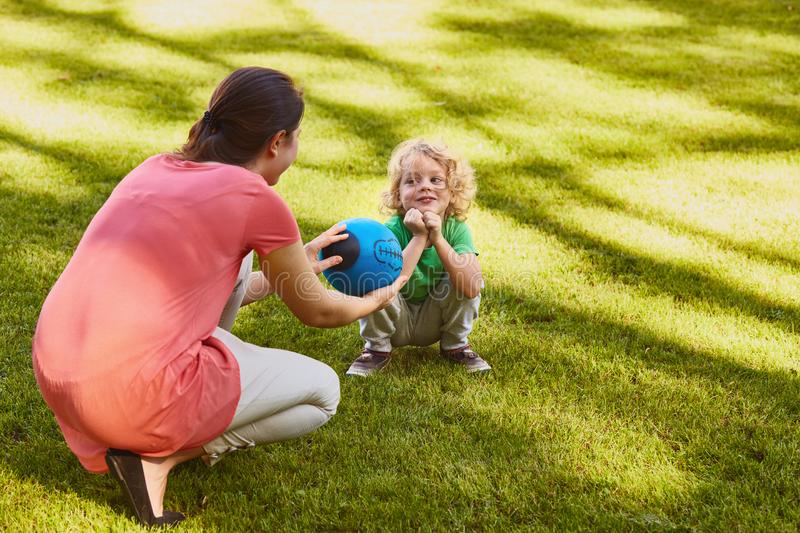 Mother giving ball to son stock image