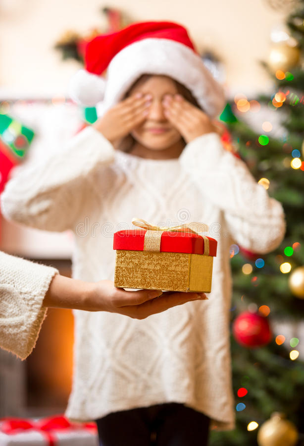 Mother giving Christmas present to daughter with closed eyes stock image