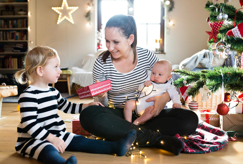Mother giving daughter Christmas present, holding her son. royalty free stock photography