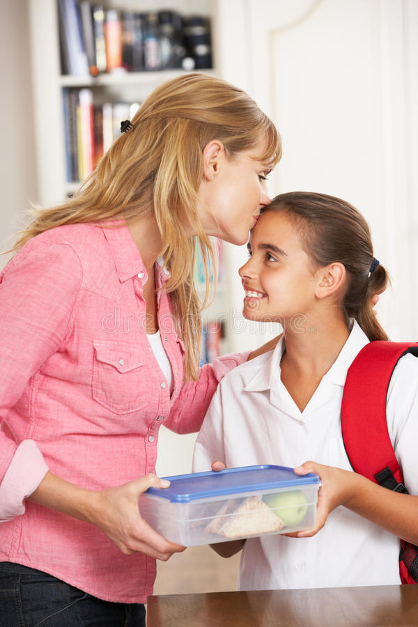Mother Giving Daughter Healthy Lunchbox In Kitchen royalty free stock photography